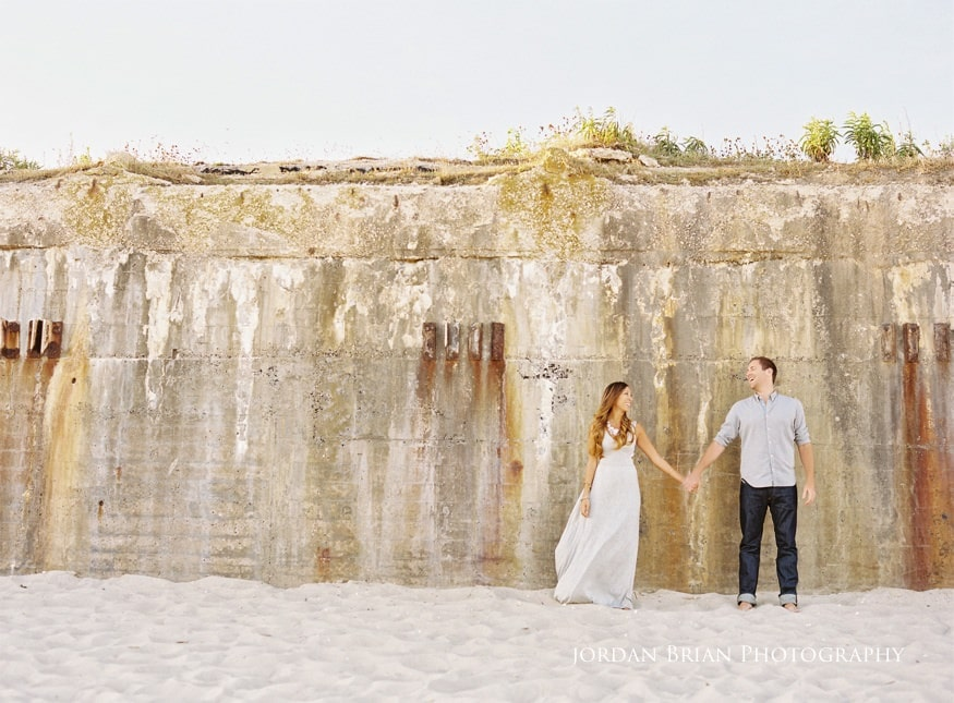 cape may engagement session couple in front of wall