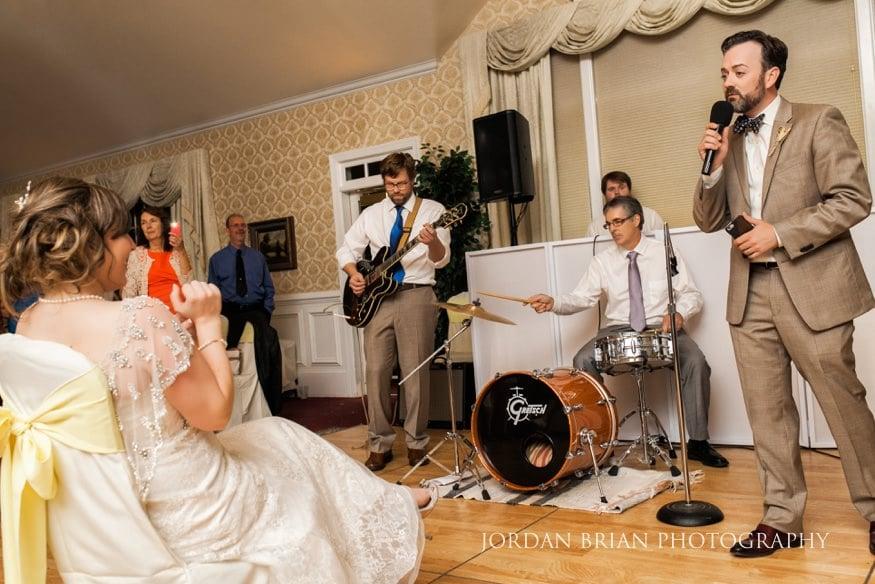 Groom singing to bride at wedding reception