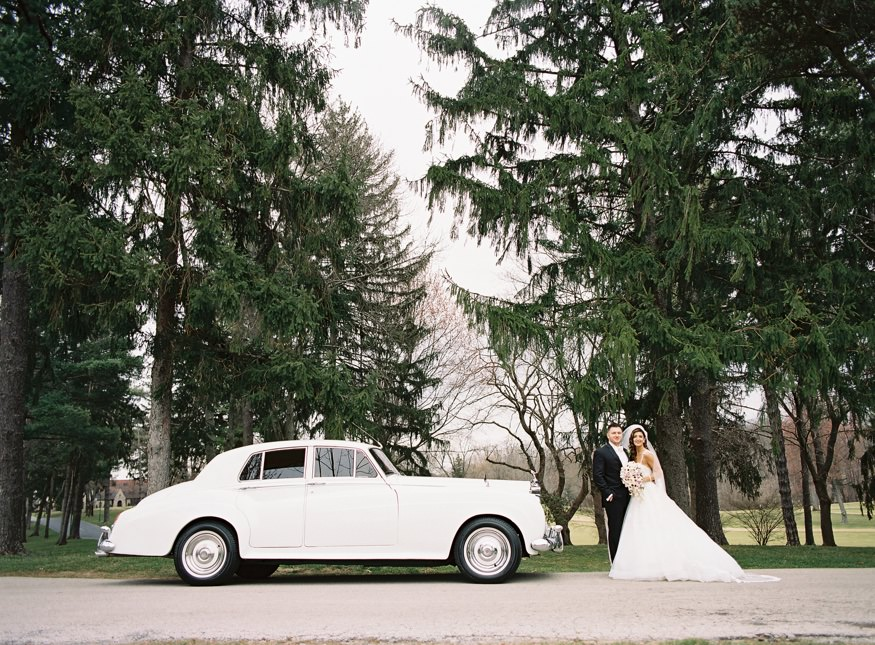 Bride and groom at Aronimink Golf Course in First Class Rolls Royce.