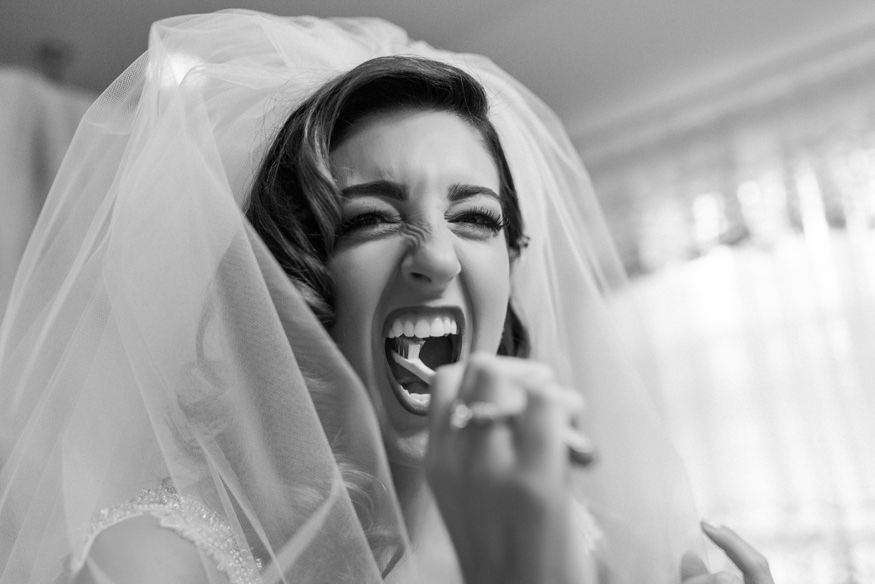Bride brushing her teeth before wedding.