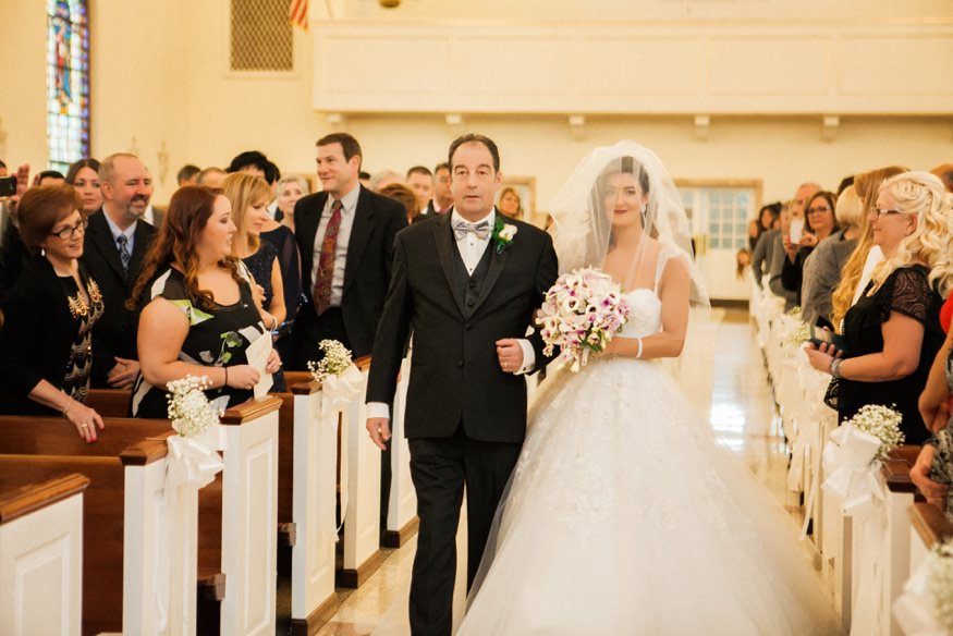Father and bride walking down the aisle at St Anastasia Church wedding ceremony.