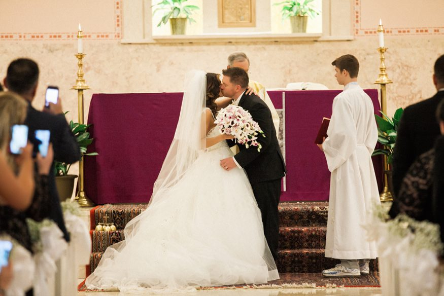 Bride and groom first kiss at St Anastasia church wedding ceremony.