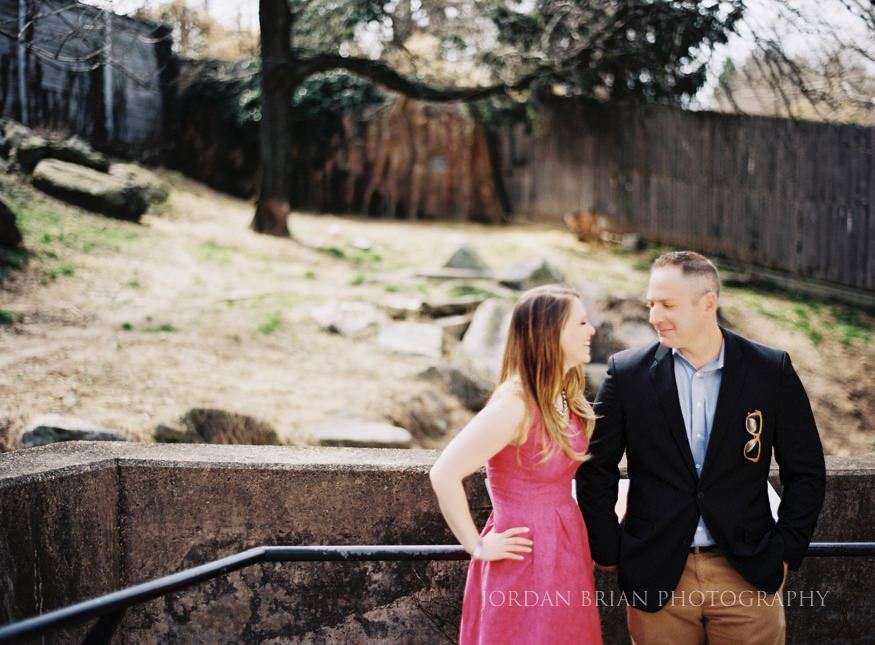 couple in front of wolf enclosure at philadelphia zoo engagment session
