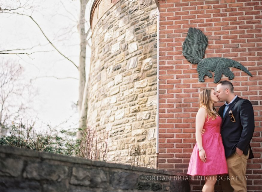 couple kissing in front of animal enclosure at philadelphia zoo engagement session