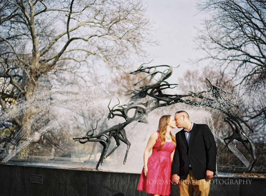 engaged couple kissing infront of fountain at philadelphia zoo