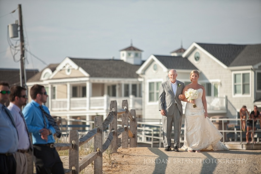 bride walking with her father to beach ceremony