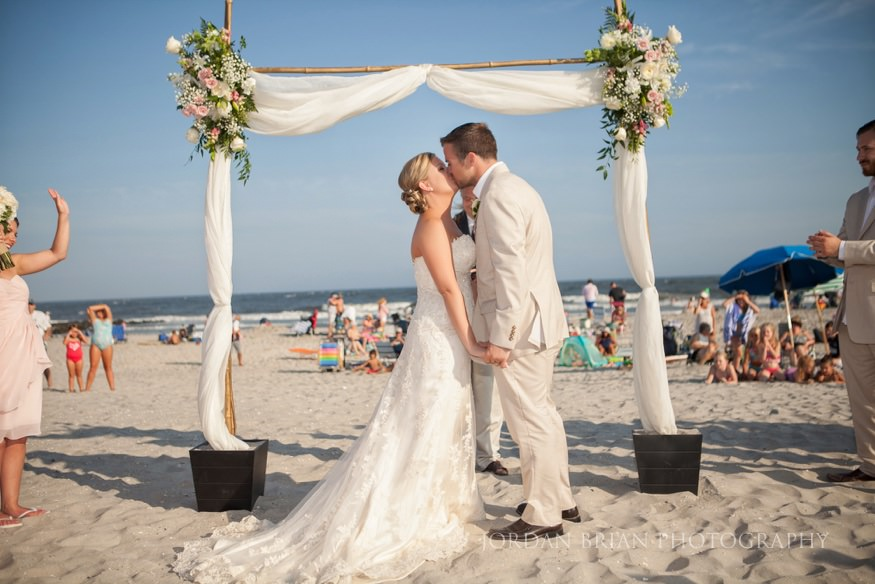 bride and groom kiss at beach ceremony at ocean city