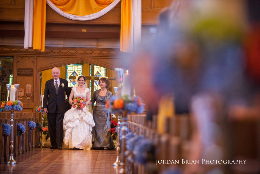 bride walking down isle with parents at st paul's catholic church in princeton nj