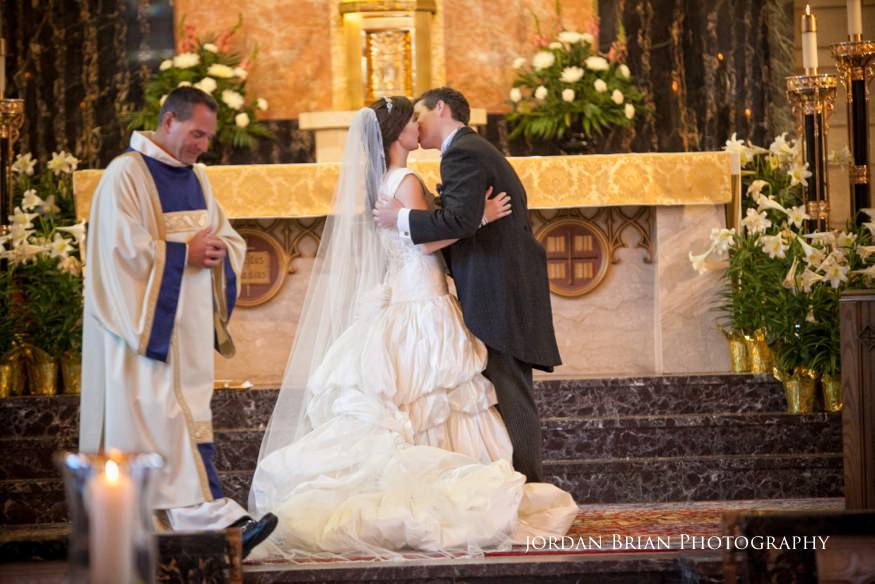 bride and groom first kiss at st paul's catholic church wedding ceremony in princeton nj