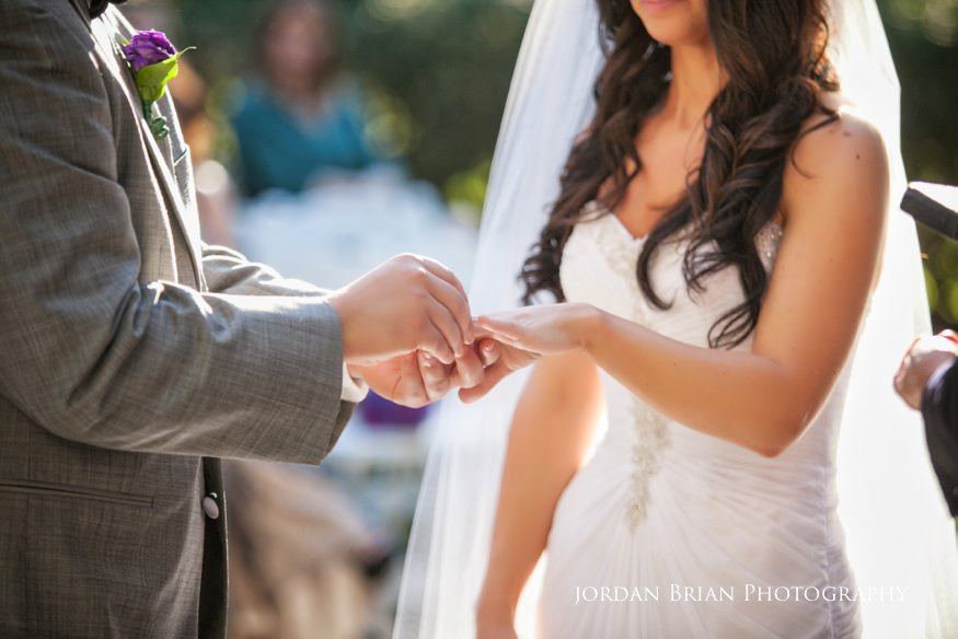groom putting ring on bride at outdoor wedding ceremony