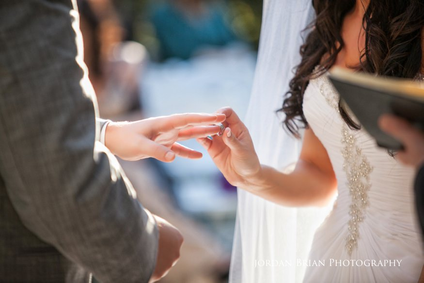 bride putting ring on groom's finger at wedding ceremony