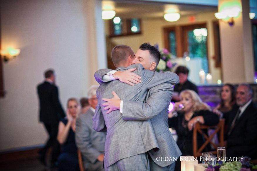 groom hugging best man after toast