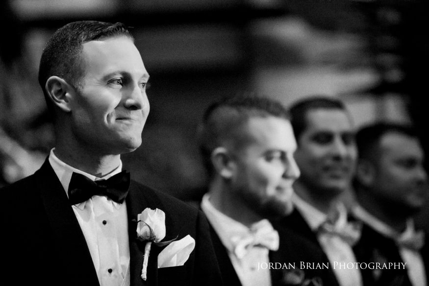 Groom looking at bride during ceremony at Fairmount Park Horticulture Center wedding.