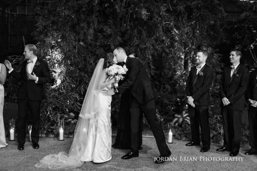Bride and groom kiss during ceremony at Fairmount Park Horticulture Center wedding.