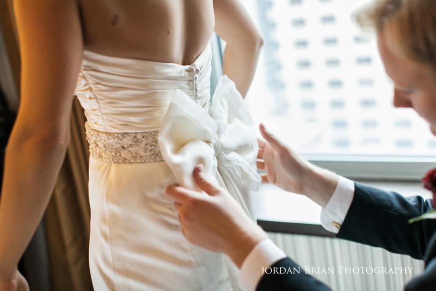 Bride fixing dress bow at Sofitel