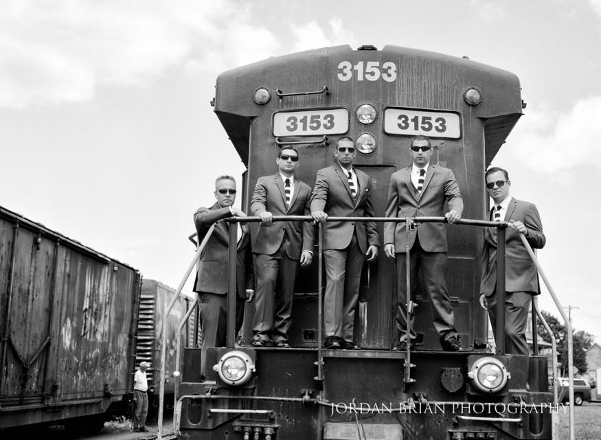 black and white film portrait of groomsmen on train