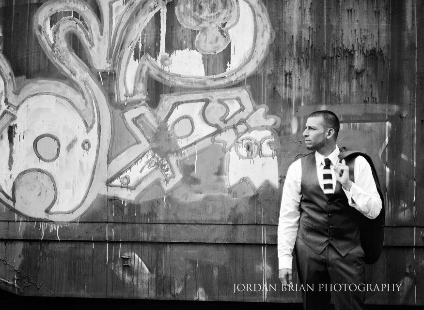 groom portrait in front of graffiti