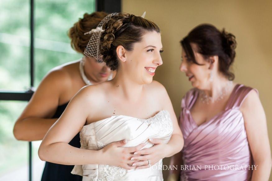 bride putting dress on at lake house inn