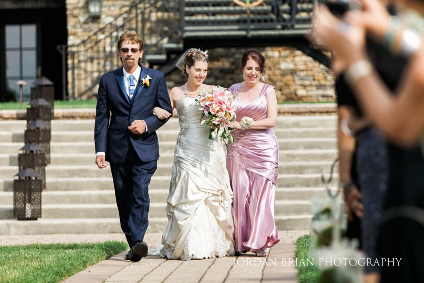 bride walking down aisle with parents lake house inn ceremony