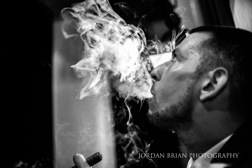 groom smoking a cigar lake house inn wedding reception