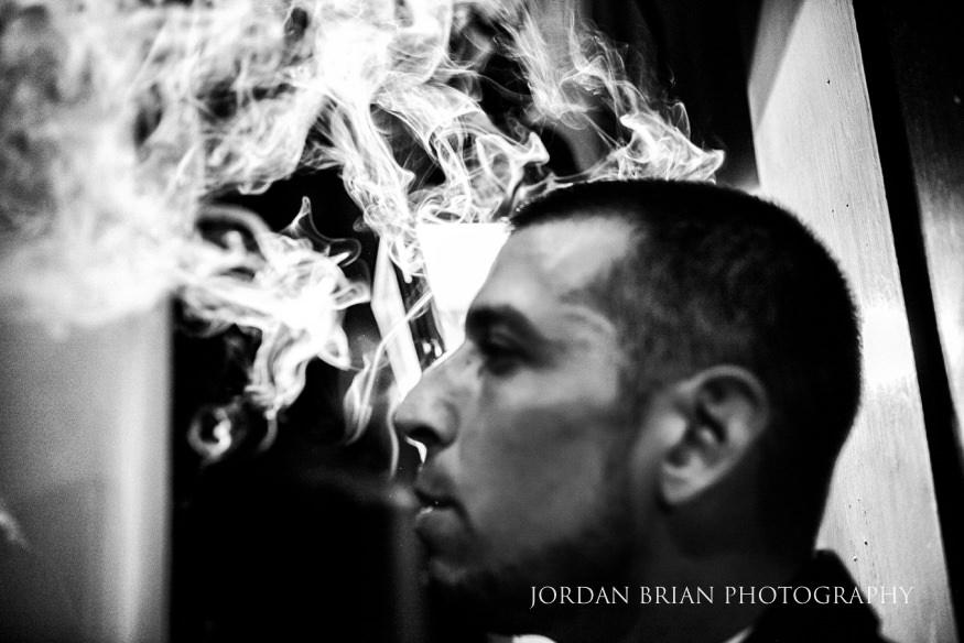 groom smoking a cigar lake house inn wedding