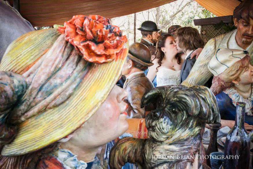 kissing bride and groom photos at grounds for sculpture with Seward Johnson exchibit